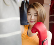 Lady boxer. An Asian lady waring red glove practicing boxing Stock Images
