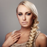 Lady with braid. Portrait of a young lady with a braid on grey background Royalty Free Stock Photos