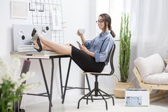 Lady during break. Beautiful young lady in glasses drinking coffee and checking her phone during break royalty free stock image