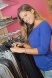 Lady browsing through rail clothes Royalty Free Stock Photos