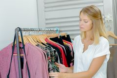 Lady browsing through rail clothes Royalty Free Stock Photography