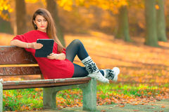 Lady browsing tablet in woodland. Outdoor technology nature autumn concept. Lady browsing tablet in woodland. Young girl sitting on bench enjoying internet on Stock Photo