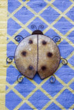 Lady Bug. A Brown and Black Giant Metal Lady Bug Climbs a Blue and Yellow Diamond Shape Pattern Brick Wall Stock Photo