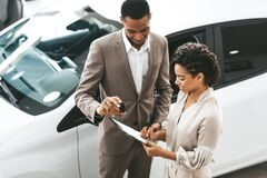 Free Lady Buying Car Signing Papers With Dealer In Dealership Store Royalty Free Stock Photos - 172739218
