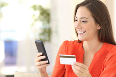 Lady buying with credit card and smart phone. Lady buying online with a credit card and smart phone sitting on a couch at home with a blurred background stock photos