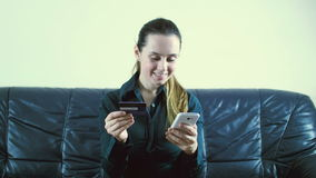 Lady buying online with a credit card and smart phone sitting on a couch at home with a blurred background stock video footage