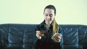 Lady buying online with a credit card and smart phone sitting on a couch at home with a blurred background stock video