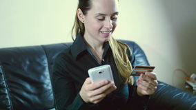 Lady buying online with a credit card and smart phone sitting on a couch at home with a blurred background stock footage