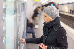 Lady buying ticket for public transport. Casually dressed woman wearing winter coat,buying metro ticket at the ticket vending machine. Urban transport stock photography