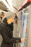 Lady buying ticket for public transport. Casually dressed woman wearing winter coat,buying metro ticket at the ticket vending machine. Urban transport royalty free stock images