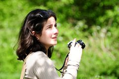 Lady With Camera. Turned to side looking out of frame at what she's about to take a photograph of with vivid green foliage background and in bright sunshine Royalty Free Stock Image