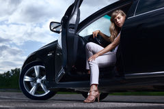 Lady and a car. Young pretty lady with a modern luxury car Royalty Free Stock Photography