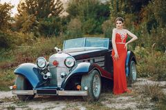 Lady in a car. Elegance lady in a red dress standing near a retro blue car Royalty Free Stock Photography