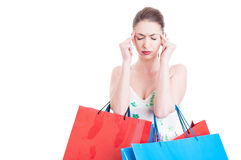 Lady carrying shopping bags and making headache gesture Royalty Free Stock Image