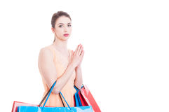 Lady carrying shopping bags posing with palms together like pray Stock Images