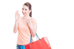 Lady carrying shopping bags swearing or promising with fingers c Stock Photos