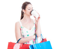 Lady carrying shopping bags taking a sip from takeaway coffee Royalty Free Stock Image