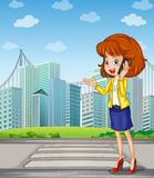 A lady with a cellphone standing at the pedestrian lane Royalty Free Stock Photo