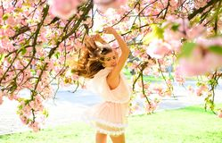 Lady with charming smile posing under Japanese cherry. Blond girl in lovely pink dress enjoying sunny day in botanical. Garden. Woman jumping in blooming spring Royalty Free Stock Image