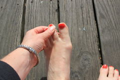 A lady checking between her toes Stock Photo