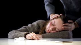 Lady checking unconscious woman suffering narcotic poisoning, drug overdose royalty free stock photography