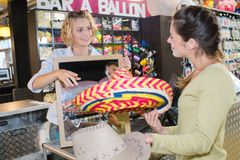 Lady at checkout with colorful sombrero hat. Sombrero Stock Photos