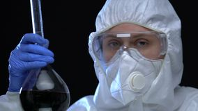 Lady chemist in uniform holding dangerous substance in flask, illegal laboratory. Stock footage stock video