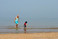 Lady and child playing in the sea Stock Photos