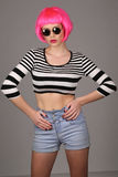 Lady with circle sunglasses and pink hair. Close up. Gray background Royalty Free Stock Image