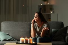 Lady claiming electric company for a blackout. Sitting on a couch in the living room at home stock images