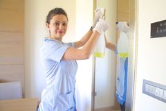 The lady is cleaning the mirror. The cleaning lady is cleaning the mirror in a hotel room Royalty Free Stock Photo