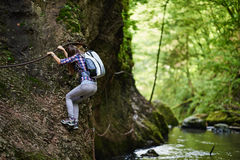 Lady climber on safety cables over river Stock Photography