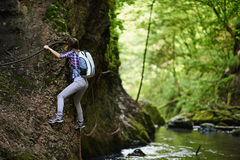 Lady climber on safety cables over river Royalty Free Stock Images