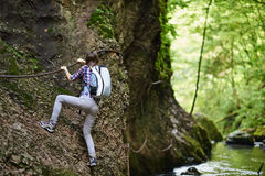 Lady climber on safety cables over river Stock Image
