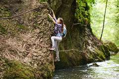 Lady climber on safety cables over river Stock Photo