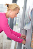 Lady collecting product from vending machine. Royalty Free Stock Images