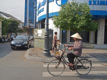 Lady with a conical hat, Vietnam. A Vietnamese lady riding on a bicycle wear a conical hat also know as no'n ba 'i tho in Vietnamese. Ideal for writeup/news Royalty Free Stock Photography
