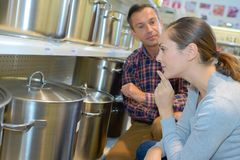 Lady contemplating large saucepans in store. Lady Stock Photo