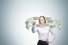 Lady is controlling cash flow of the dollar notes. Light blue background.n Royalty Free Stock Photo