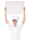Lady cook showing blank sign above head Stock Image