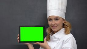 Lady in cook uniform showing prekeyed tab, proposing healthy nutrition recipes