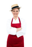 Lady cook in white red uniform wearing hat Stock Photo