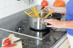 Lady cooking spaghetti pasta on her stove Stock Image
