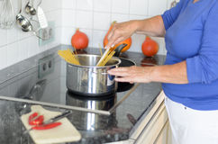 Lady cooking spaghetti pasta on her stove Royalty Free Stock Images