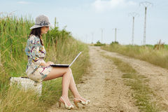 Lady on country road. Young lady with laptop spending time on a country road Royalty Free Stock Image