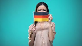 Lady covering face with German flag, learning language, education and travel. Stock footage stock video