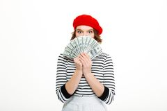 Lady covering face with money. Image of lady looking camera while covering face with money dollars isolated over white background wall stock image