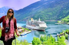 Lady with Cruise Ship on Norwegian Fjord. The cruise ship is docked in the village of Flåm in Norway. Flåm is a village at the inner end of the the fjord of Stock Photo