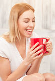 Lady with a cup of tea indoors Stock Image