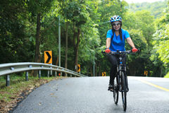 The lady is Cycling on the road Stock Photos